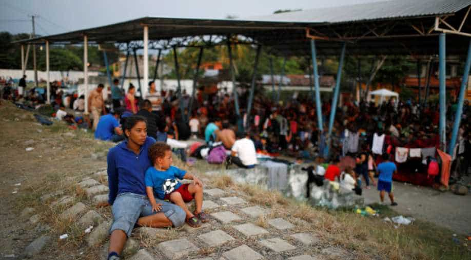 Thousands gather under a bridge on the US-Mexico border amid the growing migrant crisis