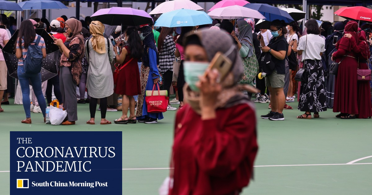 Coronavirus: Domestic workers line up outside test centers in Hong Kong from scorching heat